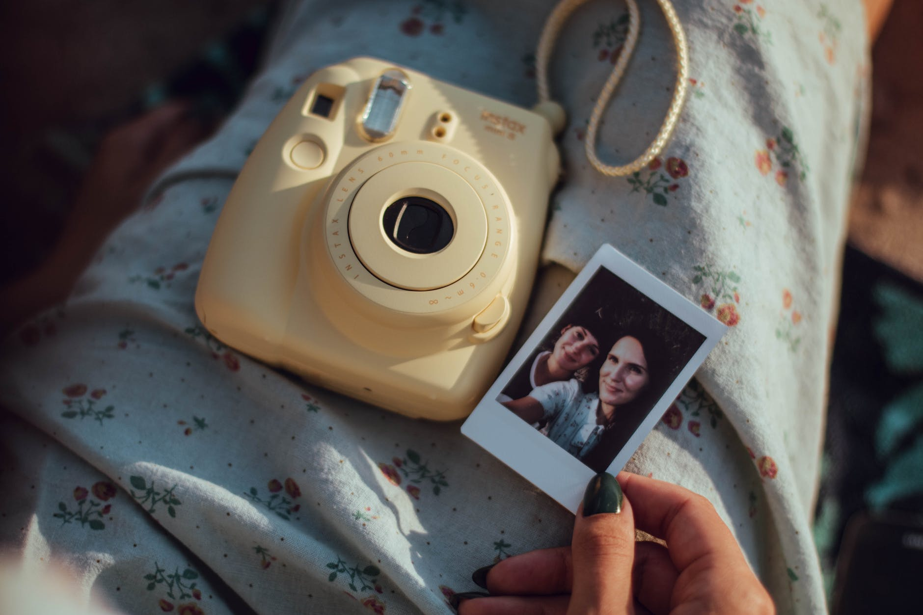 person holding woman s photo beside white fujifilm instant camera